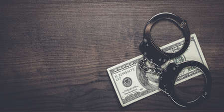 trickster: handcuffs and one hundred dollars on wooden table