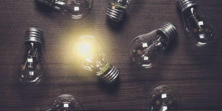 świecące żarówki nad drewnianym tle wyjątkowość koncepcji Zdjęcie Seryjne
