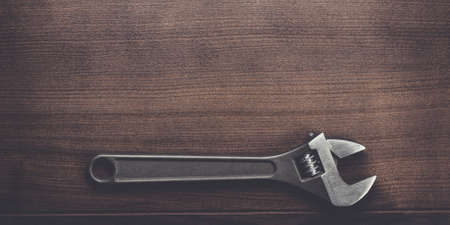 adjustable wrench on the brown wooden background