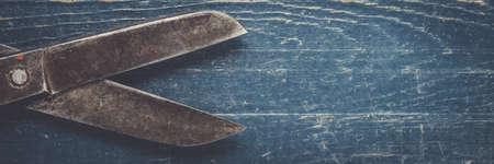 herramientas de trabajo: viejas tijeras negras en el fondo de madera Foto de archivo