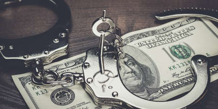 swindler: handcuffs and one hundred dollars on the wooden table