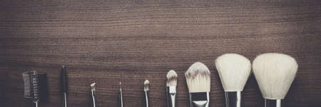 black banner: white make-up brushes on brown wooden background