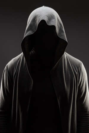 mysterious man in the hood with hidden face over dark grey background