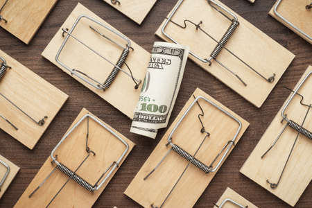 pest control: many mousetraps surrounding one hundred dollar bill. business concept Stock Photo