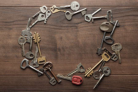 many different keys on brown wooden background with copy space in the centre Stock Photo