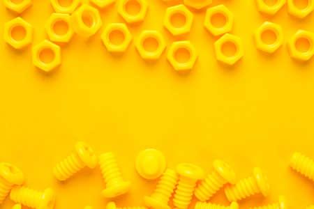 ingenieria industrial: 3d pernos impresos y nueces sobre fondo amarillo Foto de archivo