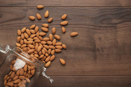 overturn: overturned glass jar full of almond seeds on the wooden table background
