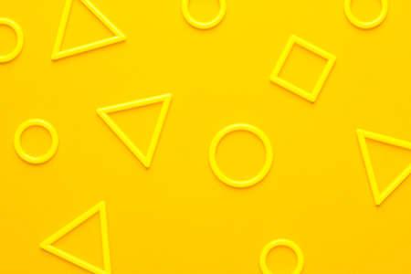 黄色の背景に異なる 3 d 印刷プラスチック幾何学的図形の写真