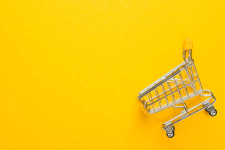 Winkelwagentje op gele achtergrond met een kopie ruimte