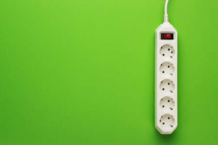 European 5-way power strip earthed on green background Stock Photo