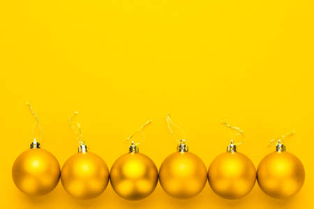 matt: Christmas tree decoration balls on yellow background with copy space