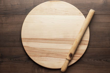 roller: old wooden rolling pin and round board on brown table Stock Photo