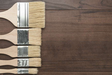 different size paint brushes on the brown wooden table Archivio Fotografico - 97503390