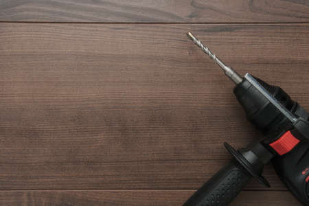 hammer drill on the wooden background with copy space Stock Photo