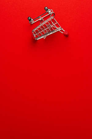 top view of overturned shopping trolley on red background. minimalist photo of pushcart with some copy space