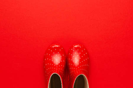 top view of watertights rain season concept. new children's stylish gumboots on red background. overhead photo of red watertights with copy space Stock Photo