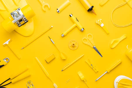 Top view of random yellow objects in order on yellow
