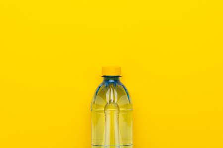 Plastic water bottle with yellow cap on the yellow 版權商用圖片
