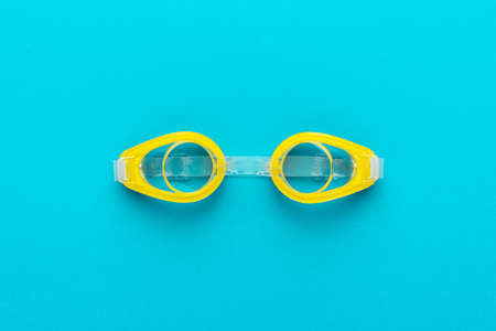 Flat lay shot of yellow swimming goggles over turquoise blue