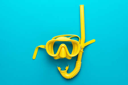 Flat lay shot of yellow diving mask with snorkel over turquoise blue