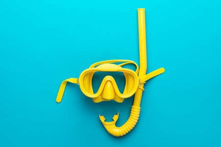 Mise à plat d'un masque de plongée jaune avec tuba sur bleu turquoise