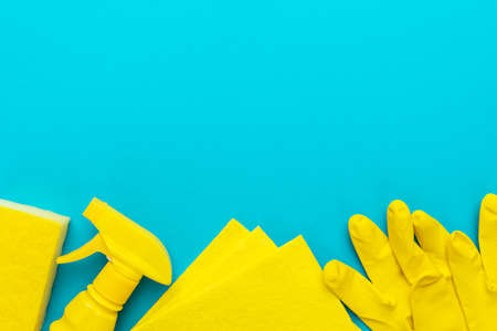 yellow cleanser in plastic container with spray, rubber protective gloves, sponge and cloths for cleaning on the turquoise blue background. flat lay image of yellow cleaning products with copy space