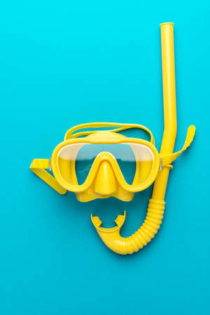 flat lay shot of yellow diving mask with snorkel over blue background. minimal conceptual photo of dive mask and snorkel central composition. flat lay of diving equipment vertical orientation Reklamní fotografie
