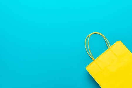 shopping paper bag on the turquoise blue background. flat lay photo of yellow bag. summer sale concept with copy space. 写真素材