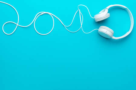 White headphones with cable. Top view of headphones on turquoise blue background. Minimalist photo of earphones with copy space. White dj headphones with cable in upper part of blue background