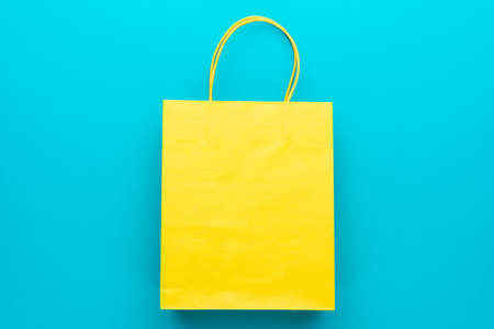 shopping paper bag on the turquoise blue background. flat lay photo of yellow bag. summer sale concept with copy space. top view of yellow shopping paper bag with central composition