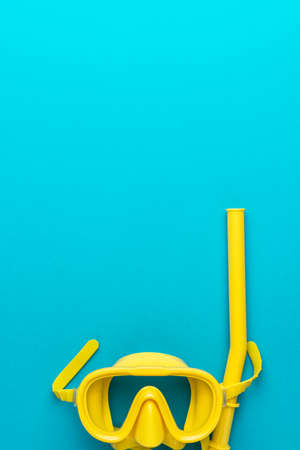 flat lay shot of yellow diving mask with snorkel over turquoise blue background. minimalist photo of dive mask and snorkel with copy space vertical orientation