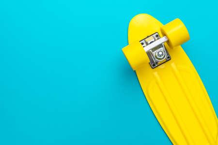 Minimalist flat lay of yellow plastic mini cruiser board on blue