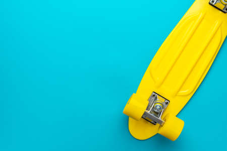 Minimalist flat lay of yellow plastic mini cruiser board on blue