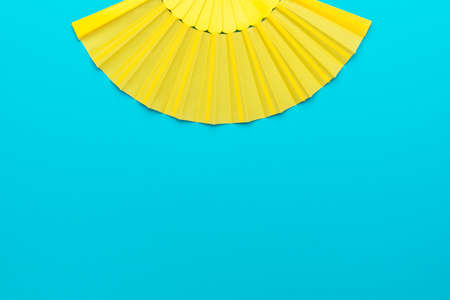 Top view of opened yellow fan over turquoise blue