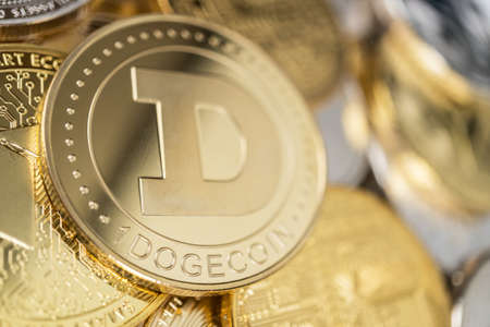Dogecoin physical coin on the stack of other different currencies. Stockfoto