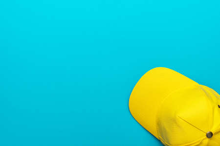Minimalist flat lay photo of the bright yellow cap with copy space.