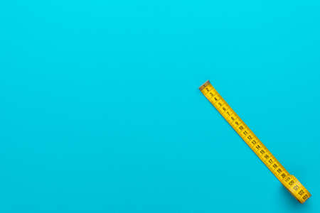 Minimalist flat lay image of tape measure with metric scale over turquoise blue 스톡 콘텐츠