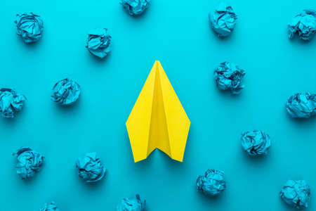 Great business idea concept with blue crumpled office paper and yellow paper plane in the centre