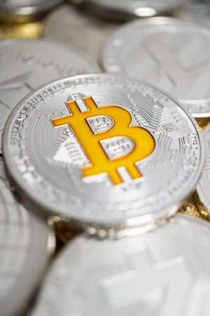 Close-up  of bitcoin with shallow depth of field. Bitcoin physical coin on the stack of other different cryptocurrencies.