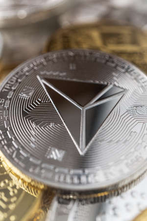 Tron physical coin on the stack of other different cryptocurrencies.
