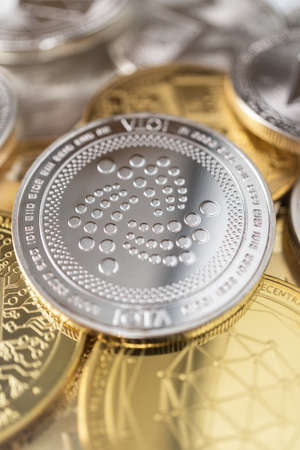 Iota physical coin on the stack of other different cryptocurrencies.
