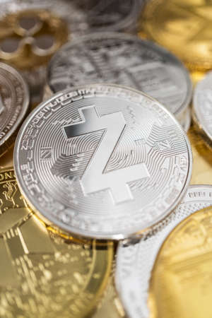 Zcash zec physical coin on the stack of other different cryptocurrencies.