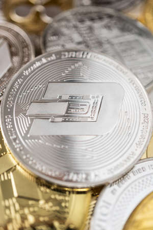 Dash physical coin on the stack of other different cryptocurrencies.