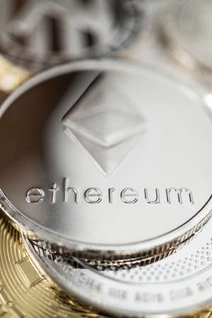 Ether physical coin on the stack of other different cryptocurrencies.