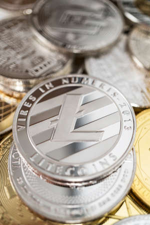 Litecoin physical coin on the stack of other different cryptocurrencies