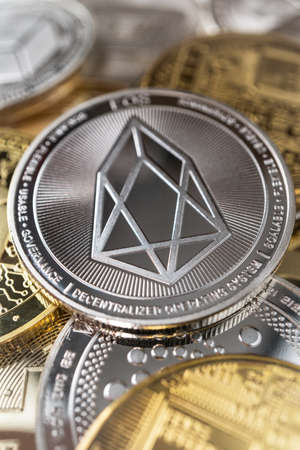 Eos physical coin on the stack of other different cryptocurrencies. Zdjęcie Seryjne