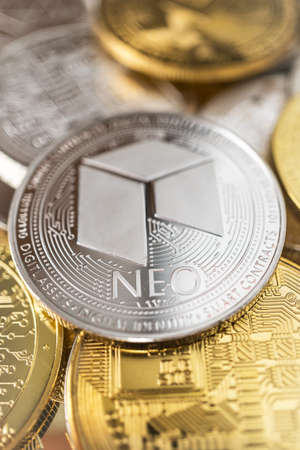 Neo physical coin on the stack of other different cryptocurrencies.