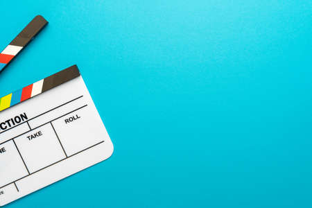 Top view of white acrylic clapperboard over turquoise blue