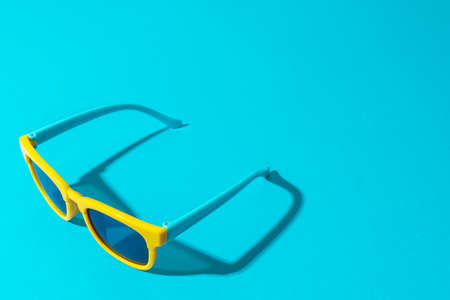 Minimalist  of stylish yellow sunglasses with harsh shadow as summer concept.