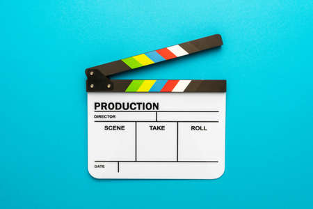 Top view  of open white clapperboard over turquoise blue